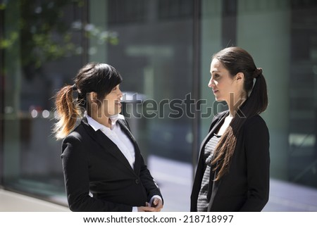 Two Happy Business women outside the office talking to each other. - stock photo