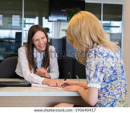 Two happy business women talking and signing credit or insurance  - stock photo