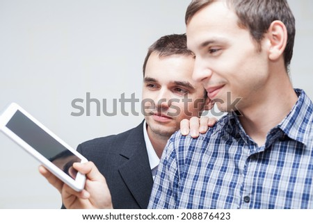 Two happy businessmen looking at digital tablet. - stock photo