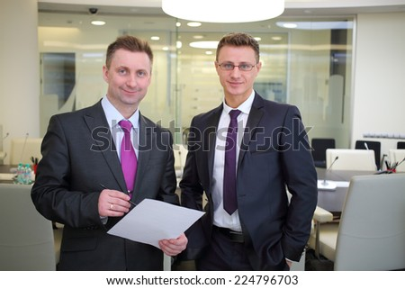 Two happy businessmen standing with a blank sheet of paper in conference hall - stock photo