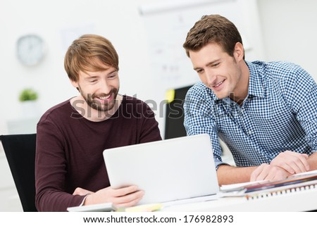 Two happy businessmen working together in the office sharing a laptop computer as they discuss a project - stock photo