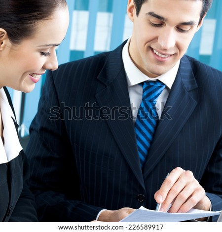 Two happy businesspeople working together at office. Focus on woman. - stock photo