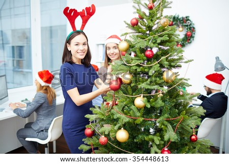 Two happy businesswomen decorating Christmas tree with red and golden bubbles - stock photo