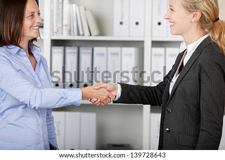 Two happy businesswomen shaking hands in office - stock photo