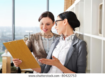 Two happy caucasian business women reading documents at their office against window - stock photo