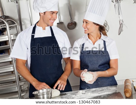 Two happy chefs looking at each other while kneading dough in commercial kitchen - stock photo