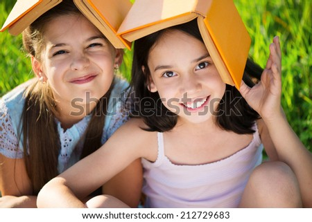 Two happy child girls studying on green grass - stock photo