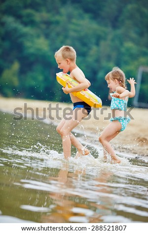 Two happy children bathing together in a lake in summer - stock photo