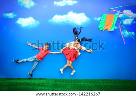 Two happy children flying together on a kite in a bright summer day. - stock photo