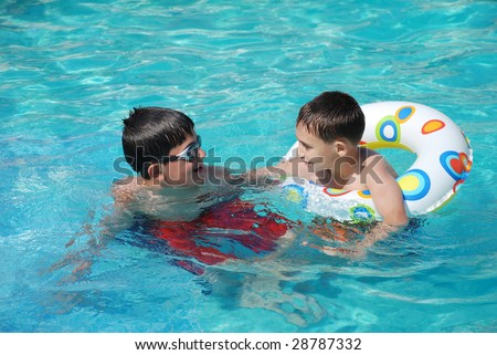 Two happy children in a swimming pool.Seven  and thirteen years old . - stock photo