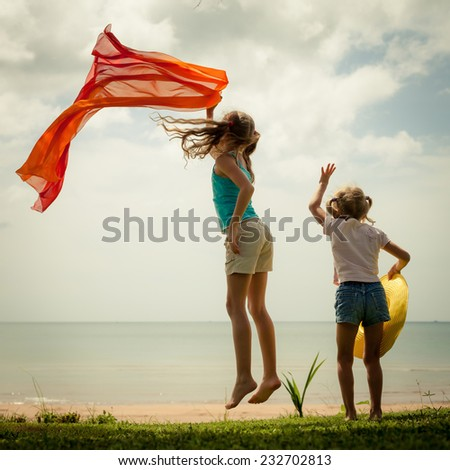 Two happy children jumping on the beach at the day time time - stock photo