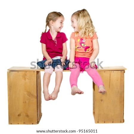 Two happy children laughing and looking at each other, isolated on a white background - stock photo