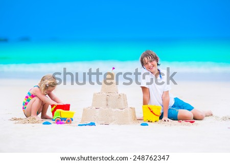 Two happy children, laughing boy and a little toddler girl in colorful swimming suit building sand castle and playing with toys on exotic tropical beach having fun at family summer vacation - stock photo