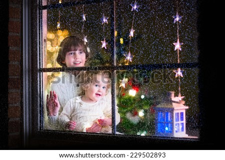 Two happy children, little curly toddler girl and laughing boy in warm knitted winter sweaters standing next to a window in a decorated living room with Christmas tree, view from outside of the house - stock photo