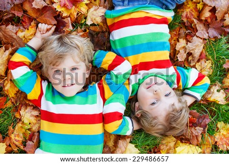 Two happy children lying in autumn leaves in colorful clothing. Happy siblings having fun in autumn park on warm day. - stock photo