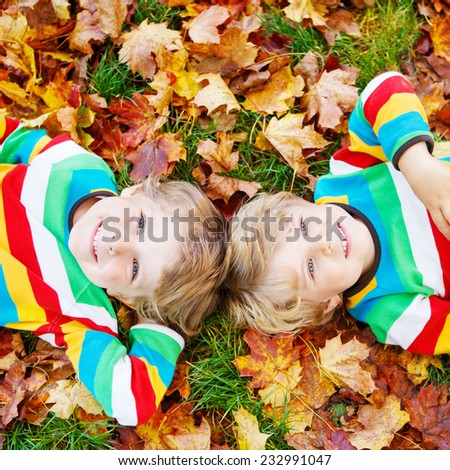 Two happy children lying in autumn leaves in colorful clothing. Happy siblings having fun in autumn park on warm day. Square format. - stock photo