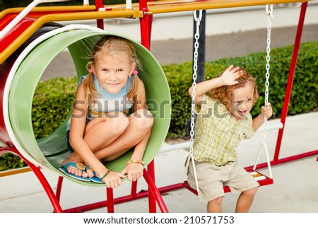 Two happy children on the playground at the day time. Concept brother and sister forever. - stock photo