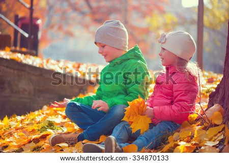 Two happy children playing in autumn park - stock photo