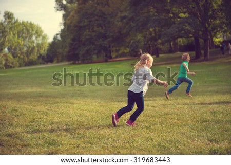 Two happy children running in park in sunset - stock photo