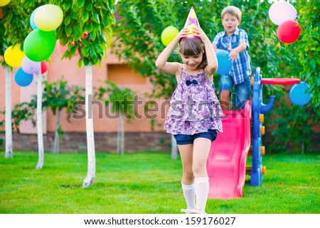 Two happy children sliding at playground during birthday party - stock photo