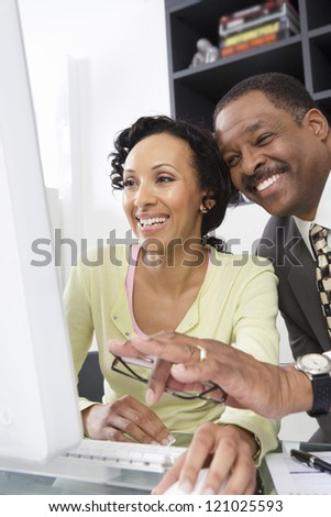Two happy colleagues laughing in front of computer at office - stock photo