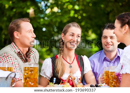 Two happy couple sitting in Beer garden and enjoy the beer and the sun - stock photo