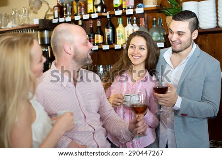 Two happy couples hanging out in a bar drinking coffee, wine and cognac - stock photo