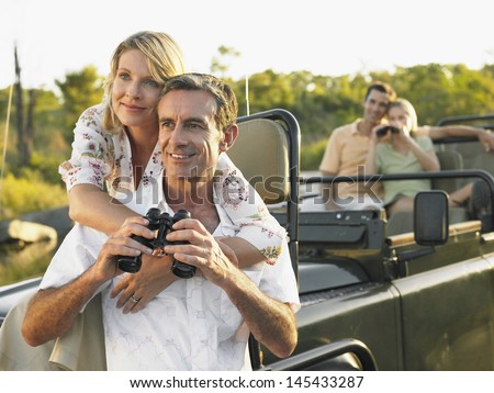 Two happy couples on trip with binoculars in jeep - stock photo