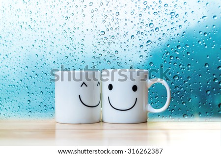 Two happy cups on the wood table with a glass surface windows, about love concept - stock photo