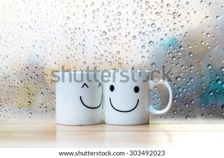 Two happy cups on the wood table with glass surface windows, about love concept - stock photo