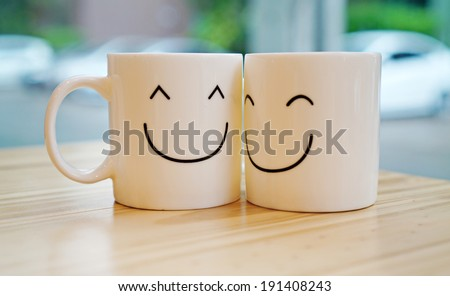 Two happy cups with black polka dot tablecloth. Concept about love and relationship - stock photo