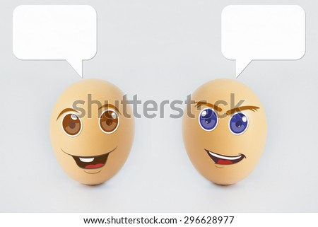 Two happy eggs with smiling faces representing emotional happiness with speech bubble for text caption. Isolated on a white background - stock photo