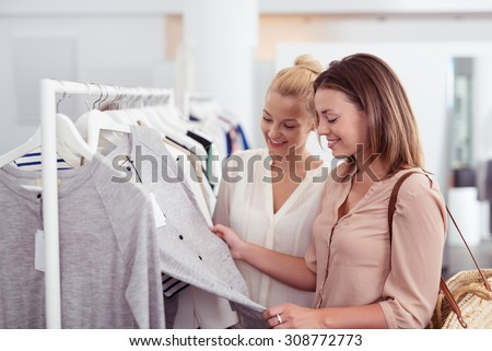 Two Happy Female Best Friends Looking at the Quality of a Gray Shirt Hanging on a Rail inside the Clothing Store. - stock photo