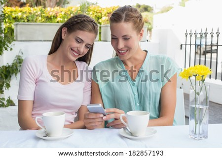 Two happy female friends reading text message at the coffee shop - stock photo