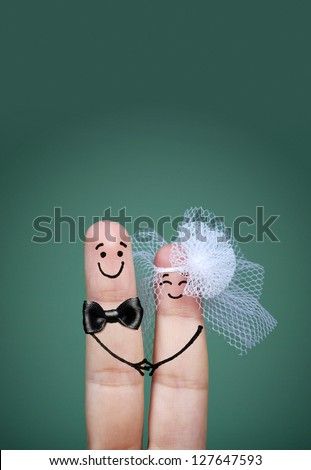 Two happy fingers decorated as bride and groom with veil and bow tie - stock photo