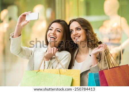 Two happy friends is taking selfie while shopping in mall. - stock photo