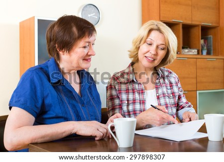 Two happy friends sitting at the desk and signing contract - stock photo