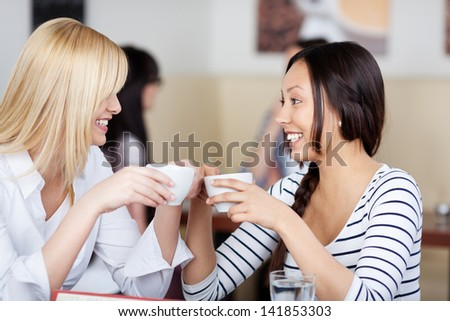 two happy friends talking in a cafe and drinking coffee - stock photo