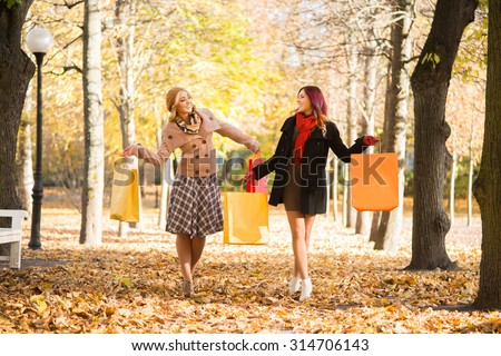Two happy friends with shopping bags walking through the park in the autumn. - stock photo