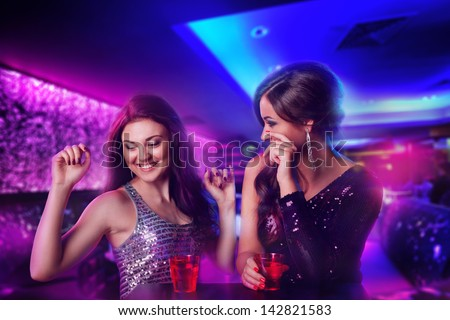Two happy girl friends at the club, laughing and drinking - stock photo