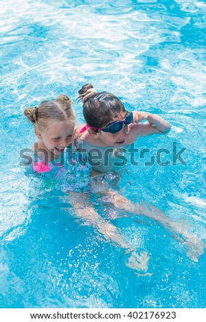 Two happy girlfriends girls playing in the pool with one another  - stock photo
