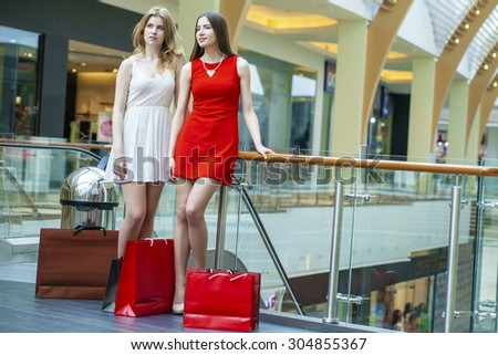 Two happy girlfriends on shopping walk on shopping mall with bags - stock photo