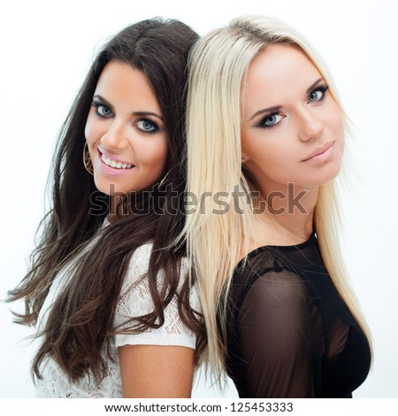 Two happy girlfriends posing on white background - stock photo