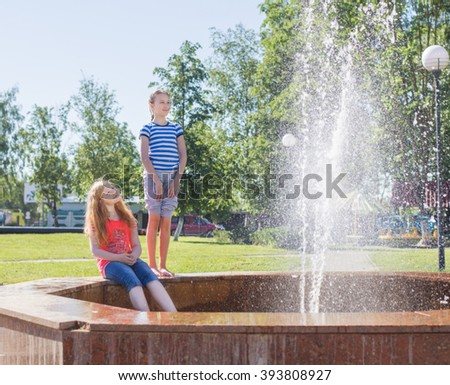 two happy girls at the fountain - stock photo