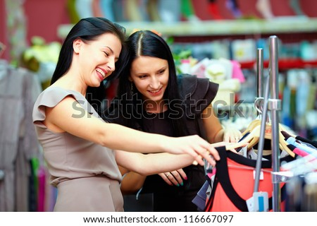 two happy girls buy dress on store sale - stock photo