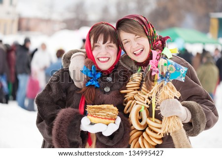 Two happy girls celebrating  Pancake Week at Russia - stock photo