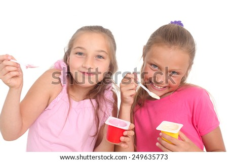 two happy girls eating yogurt - stock photo