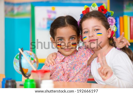 Two happy girls in international summer camp with flags on cheeks - stock photo