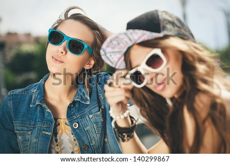 Two happy girls in sunglasses looking into the distance on the urban background. Young active people. Outdoors - stock photo