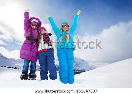 Two happy girls outside on winter day standing together with lifted hands - stock photo